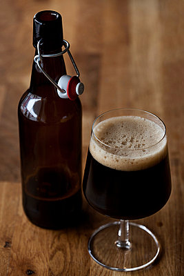 Craft beer bottle and glass on wooden table - p426m1003844f by Fredrik Telleus