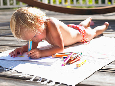 Little girl drawing a picture in the sun - p4292519f by Ghislain & Marie David de Lossy