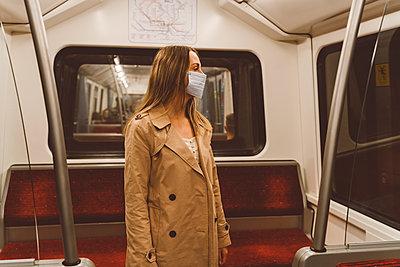 Junge Frau mit Mundschutz unterwegs mit der U-Bahn - p432m2184852 von mia takahara