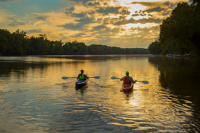 Couple kayaking in river at sunset - p555m1304532 by WHL