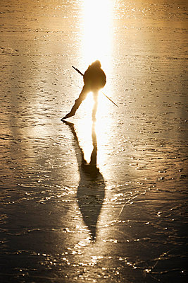 Person ice-skating on frozen lake - p575m711010f by Henrik Trygg