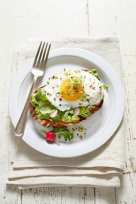 Avocado toast with radish, fried egg and micro greens - p924m1494905 by Ryan Benyi Photography