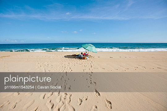 Mid distance view of father and children at beach against sky - p1166m1543254 by Cavan Social