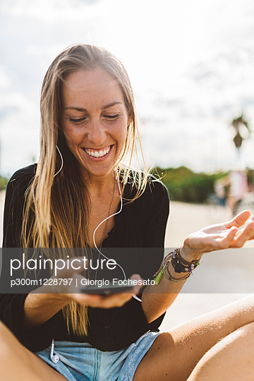 Happy young woman with cell phone and earbuds outdoors - p300m1228797 by Giorgio Fochesato