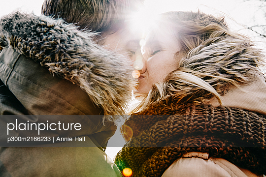 Kissing young couple in winter at backlight - p300m2166233 by Annie Hall