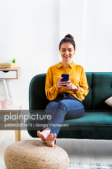 Young woman smiling while using mobile phone sitting on sofa at home - p300m2251473 by Giorgio Fochesato