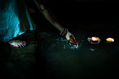 Woman pushing a candle in the river at night - p1007m1144323 by Tilby Vattard
