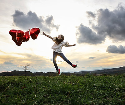 Little girl with red balloons jumping around - p1019m1496303 by Stephen Carroll
