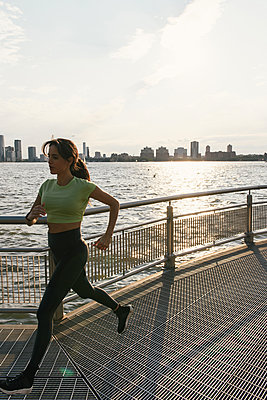 Full body image of jogger running over foot bridge by riverfront - p1166m2292584 by Cavan Images