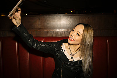 Confident, cool female millennial taking selfie with smart phone in nightclub - p1192m1583721 by Hero Images
