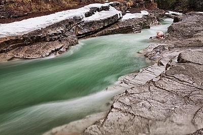 Nackter Mann kauert am steinigen Ufer eines Baches - p1383m1355302 von Wolfgang Steiner