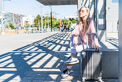Spain, Barcelona, young woman with trolley bag waiting at station - p300m2069901 von Giorgio Fochesato