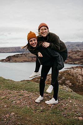 UK, Scotland, Highland, happy woman carrying friend piggyback in rural landscape - p300m2104036 by letizia haessig photography