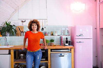 Portrait of smiling woman standing in office kitchen - p300m2114248 by Florian Küttler