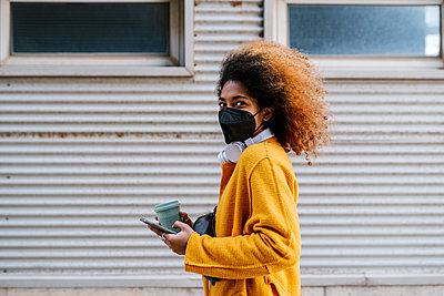 Young woman with coffee cup holding mobile phone while standing by wall during pandemic - p300m2265827 by Ezequiel Giménez