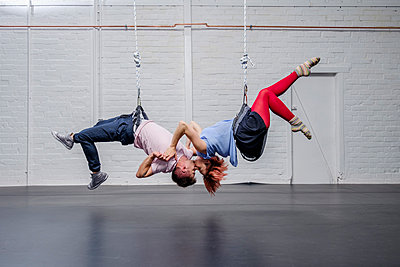 Modern aerialist dancers performing, hanging upside-down and kissing - p301m2075715 by Sven Hagolani