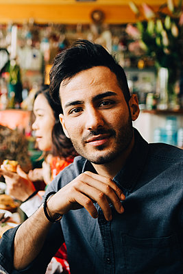 Portrait of confident young man sitting at table in restaurant during dinner party - p426m2046329 by Maskot
