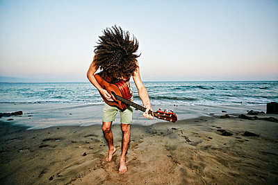 Mixed Race man tossing hair and playing guitar at beach - p555m1301729 by Peathegee Inc