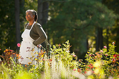 Mixed race woman wearing apron in field - p555m1480033 by Mark Edward Atkinson/Tracey Lee