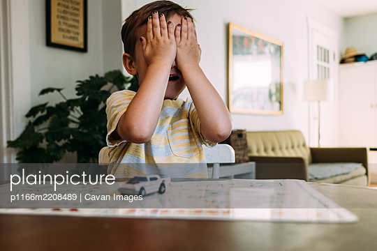 Toddler sitting at table playing peekaboo and covering his eyes - p1166m2208489 by Cavan Images