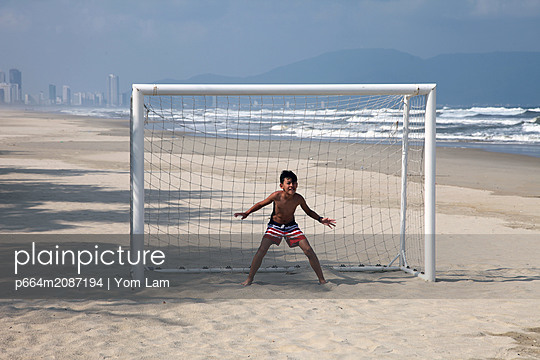 Young Goal keeper during a football match on the beach - p664m2087194 by Yom Lam