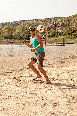 Croatia, Young man on beach playing soccer - p1026m762668f by Dario Secen
