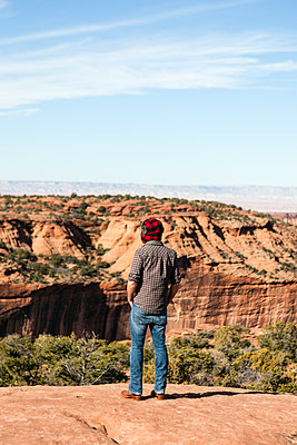 Rear view of man standing on rock at Canyon de Chelly against sky - p1094m1209092 by Patrick Strattner