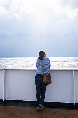 Woman on ship looking at sea - p280m1111790 by victor s. brigola