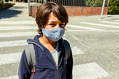 Schoolboy wearing mask standing on road during sunny day - p300m2214162 by Valentina Barreto