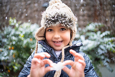 Cute smiling girl holding flower during snowfall - p300m2252603 by Ignacio Ferrándiz Roig