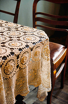 Detail of crocheted lace tablecloth with dining chairs - p349m790489 by Polly Eltes
