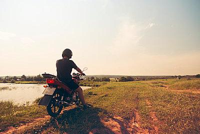 Caucasian man riding motorcycle in rural field - p555m1411142 by Aleksander Rubtsov