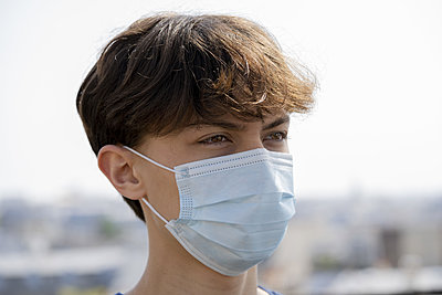 Close up of teenage boy wearing blue surgical mask outdoors - p623m2186273 by Frederic Cirou
