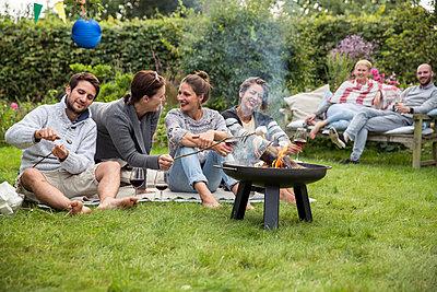 Freunde auf einer Gartenparty rösten Marshmallows  - p788m1165404 von Lisa Krechting