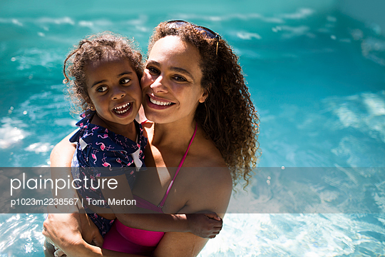 Portrait happy mother and daughter in sunny summer swimming pool - p1023m2238567 by Tom Merton