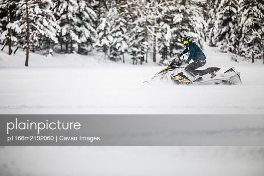 active man snowmobiling through deep snow during weekend getaway. - p1166m2192060 by Cavan Images