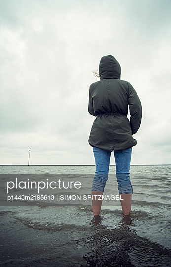 Woman standing by the sea - p1443m2195613 by SIMON SPITZNAGEL