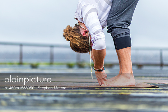 Man practicing yoga on a pier along the waterfront of Elliott Bay, Seattle