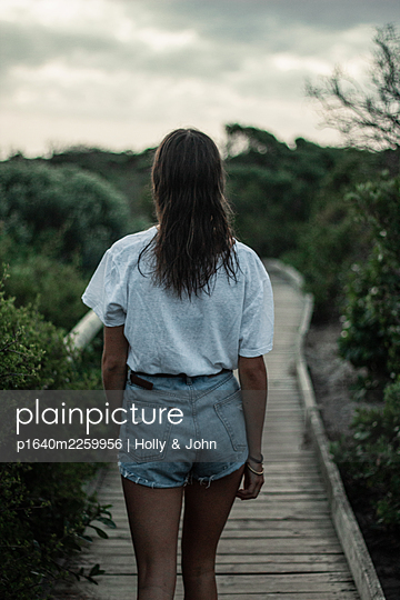 Young girl on wooden boardwalk - p1640m2259956 by Holly & John