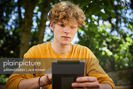 Portrait of young man using digital tablet outdoors - p300m2202621 by Jo Kirchherr