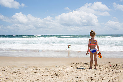 Rear view of girl looking at brother playing in sea against cloudy sky - p1166m1404028 by Cavan Images