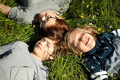Drei Jungen liegen auf einer Wiese in der Sonne - p1195m1138108 von Kathrin Brunnhofer