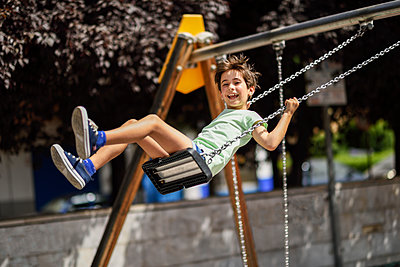 Portrait of happy little girl having fun on a swing - p300m2029530 von Javier Sánchez Mingorance