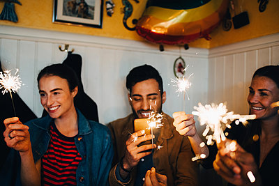 Young multi-ethnic male and female friends holding burning sparklers in restaurant during dinner party - p426m2046300 by Maskot