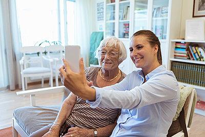 Smiling senior woman and granddaughter taking selfie using mobile phone during visit in nursing home - p426m2072584 by Kentaroo Tryman