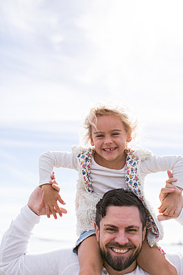 Portrait of mature man giving daughter a shoulder carry at coast - p924m1404190 by Sasha Gulish