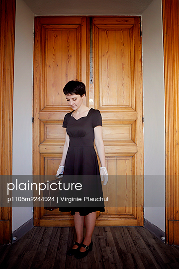 Woman in black dress and suitcase - p1105m2244924 by Virginie Plauchut