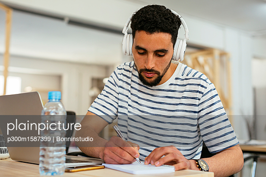 Young man wearing headphones taking notes at desk in office - p300m1587399 von Bonninstudio