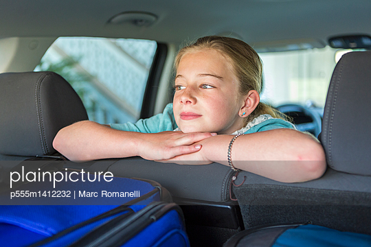 Caucasian girl sitting in car back seat on road trip - p555m1412232 by Marc Romanelli