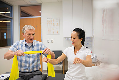 Physical therapist guiding patient with resistance band - p1192m1050572f by Hero Images